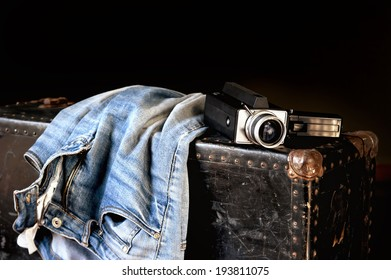 Pair of jeans and old movie camera on a vintage suitcase