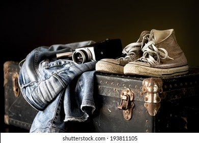 Pair of jeans sneakers and old movie camera on a vintage suitcase