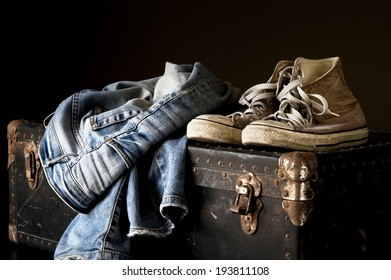 Pair of jeans and sneakers on a vintage suitcase