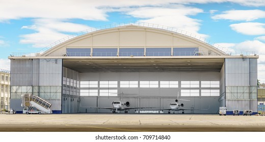 A pair of jets parked in a hangar.