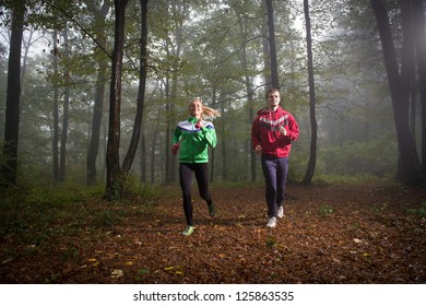 pair jogging in autumnal woodland with fog
