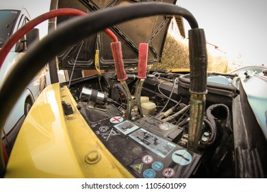 A pair of jumper or starter cables connected to a dead battery in a yellow vintage car. Concept of roadside assistance on old cars.