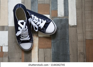 Pair of keds on color wooden background with free space