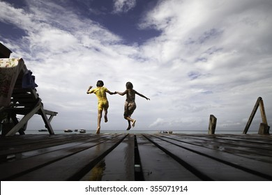 A pair of kids jumping together in sea at Mabul Island