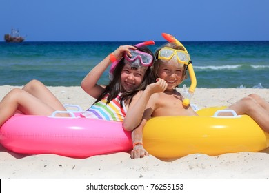 A pair of kids sitting on the beach.