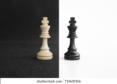 Pair of king chess peaces confronted as opposites in black and white background.