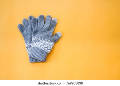 A Pair of Knitted Gloves on Orange Background Top View