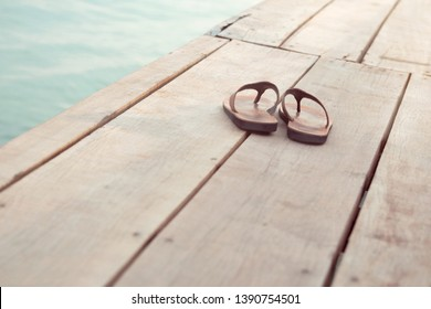 A pair of leather flip-flops on wooden planks next to the water