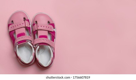 Pair of leather sandals  on pink background with copy space. Pink baby girl summer sandals. Trendy comfortable shoes for summer. Toddler fashion footwear concept. Place for text.