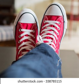 Pair of legs crossed with feet wearing red converse shoes