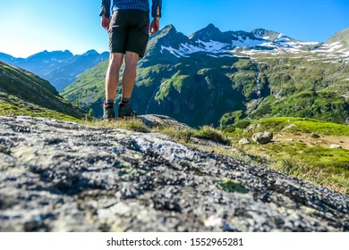 A pair of legs in hiking boots and shorts standing at the edge of a rock with a mountain view in front. Beautiful mountain view. Slopes are partially covered with snow. Austrian Alps, Schladming
