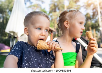 Pair of little cute adorable playful caucasian blond children sharing sweet tasty ice cream on hot summer day outdoors. Two happy sibling kid enjoy dessert during vacation holiday beach pool together