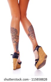 A pair of long and sexy legs with tattoos along calves