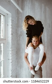 A pair of lovers, hug, kiss, laugh and have fun. The girl in long black sweater and white high golf. The girl sits on the shoulders of the guy. Light gray interior, large window, brown stylish chair.
