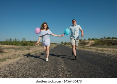Pair of Lovers Running Along the Road With Balloons in Their Hands. Spring season, April.