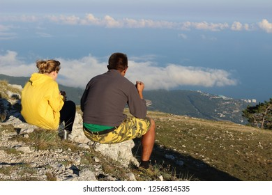 A pair of lovers tourists dine on top of Mount Ai-Petri on the Black Sea coast, above the clouds, Crimea, Russia. The best lunch in nature