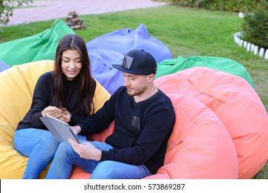 Pair of lovers of young attractive people sitting in soft yellow and red chair, man uses gadget that keeps in arms, female holds plastic card, coupon. Young people cute communicate, plan to travel