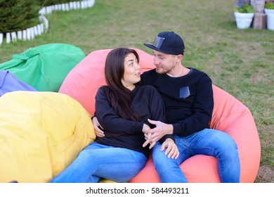 Pair of lovers of young attractive people sitting in soft yellow and red chair.  Young people cute communicate, plan to travel, choosing interior of apartment, guy tells about one of following genera