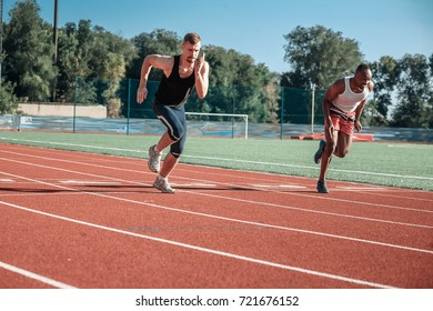 A pair of male athletes compete in a race at the stadium