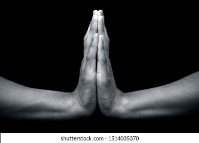 Pair of male hands isolated on black joined and doing Anjali mudra of namaste. Horizontal shot.