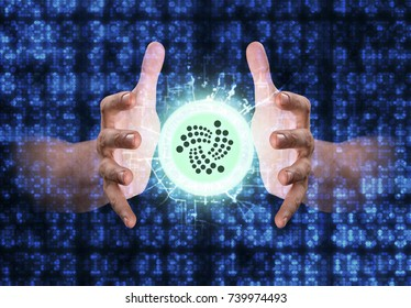 A pair of male hands reaching through digital numerical data figures grasping at an Iota coin hologram