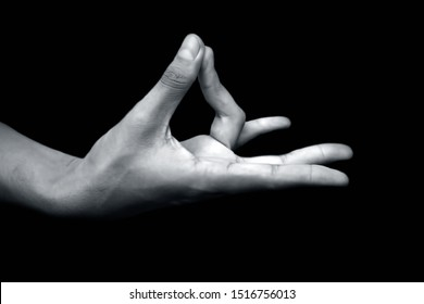 Pair of male teenager's hand doing Prithivi Mudra or Earth mudra Yoga hand gesture isolated on black which connects the root chakra aligning it with earth energies.