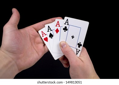 A pair of man hands hold four aces against a black background.