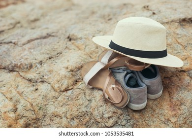 Pair of man and woman shoes and hand on a sandy sea beach. Summer vacation concept
