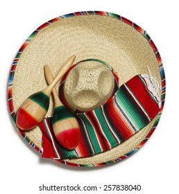 A pair of maracas and a colorful Mexican blanket on a sombrero on a white background