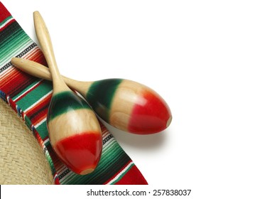 Pair of maracas and a sombrero on a colorful Mexican blanket on a white background