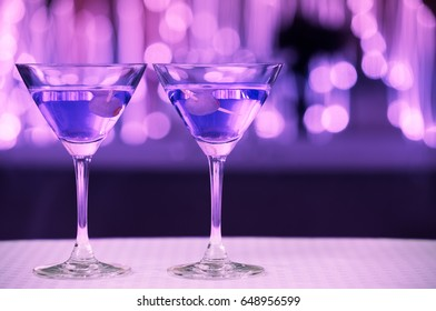 Pair of martini drinks against a sparkling backgroud.