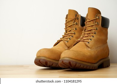 Pair of  Men yellow boots is on wood table.