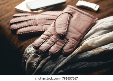 Pair of men's brown leather gloves and other men's accessories on wood background.