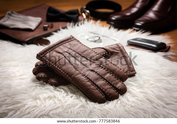 白い毛皮の上に男性用の茶色の皮の手袋と他の男性用アクセサリーを2組。