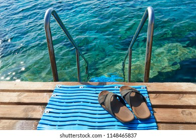 A pair of mens leather sandals by steps leading to sea