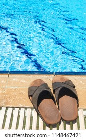 A pair of mens leather sandals by side of swimming pool