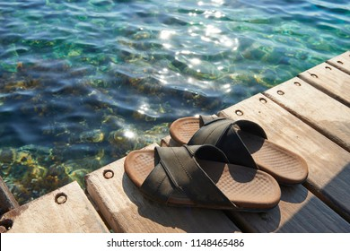 A pair of mens leather sandals on water's edge by sea