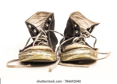 Pair of Men's or Teenager's Grundy Worn Out Dirty High Top Athletic Tennis Shoes with Long Laces Isolated on White Background
