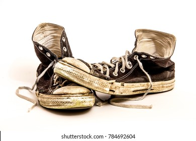 Pair of Men's or Teenager's Grungy Worn Out Dirty High Top Athletic Tennis Shoes with Long Laces Isolated on White Background