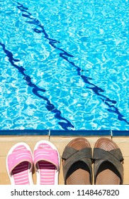 A pair of mens and womans sandals by side of swimming pool