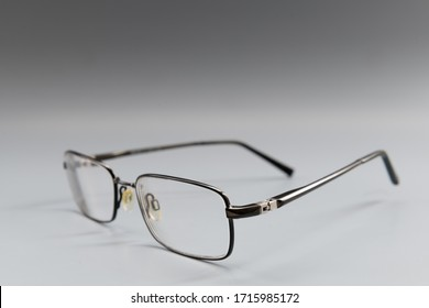 A pair of metal framed prescription eye glasses on a grey surface/ background set at an angle showing the lenses and the entire frame.