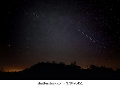 Pair of Meteors. Meteor Shower Night Sky Landscape Silhouette. Shooting Stars