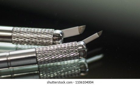 A pair of microblading pens with blades