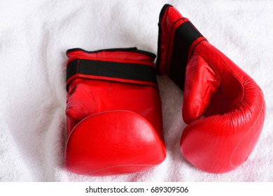 Pair of mittens for boxing in red color and traditional style on white towel background, top view. Concept of sportive equipment