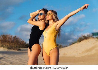 A pair of models in yellow and black swimsuit wearing sunglasses posing on the beach near the ocean. Couple of beautiful girls hug and enjoy the rest. Two sexy blondes with beautiful bodies are