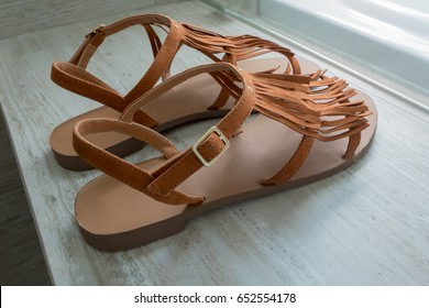 A pair of modern brown leather sandals on marble background.