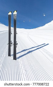 Pair of modern carving skis standing on newly groomed ski piste.