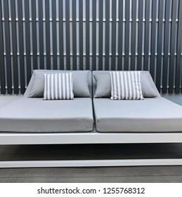 Pair of modern sun loungers against an abstract metal designer wall