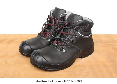 pair of new black work boots made of genuine leather with a reinforced cape, the concept of special shoes for different professions