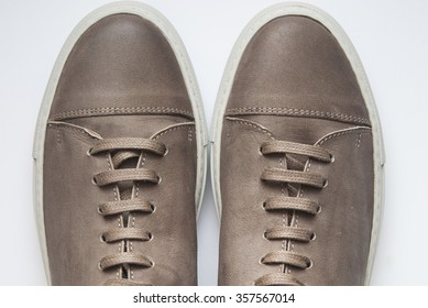Pair of new, male, casual style gym shoes that are made of brown leather, with brown shoelaces, on white background